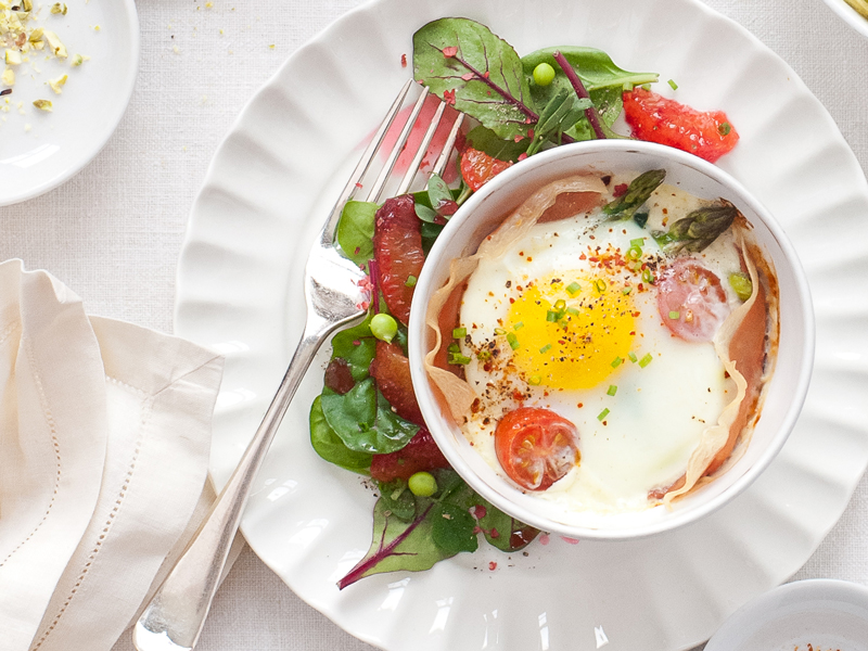 Baked eggs in ramekin dish with green salad on a plate