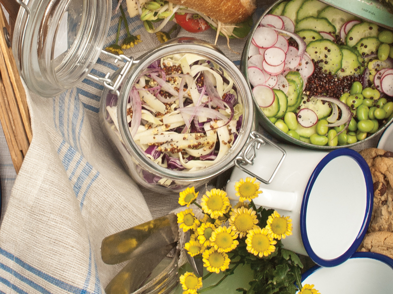 Containers of salad and flowers in a picnic basket
